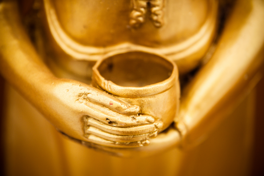 Golden Buddha holding empty cup